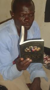 South Sudanese Pastor reading a John Piper book.