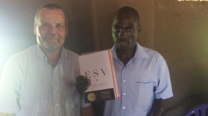 Pastor Bosco receiving a ESV Study Bible and several Christian books.