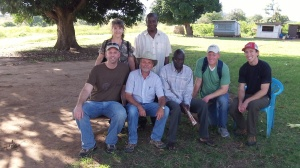 "At the Ugandan/South Sudan border with the ""Tennessee Trio"". Seated: David, Jacob,Officer in Charge of Afoji Border Crossing, Michael, Eric.Standing: Carol, Immigration Officer"