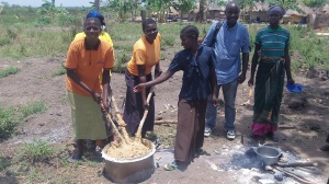 Sam with some of cooks. They are mingling cassava flour which is the main food Obongi